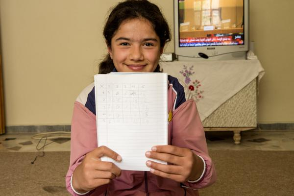 Dilan, a bright 13 year old, proudly shows her mathematics work taugh at a Save the Children child friendly space established in Suruç. Photo Ahmad Baroudi