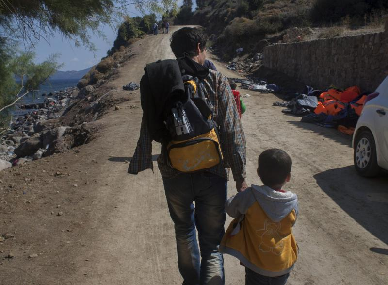 A father leads his son away from the beach at Skala Sikamineas, Greece