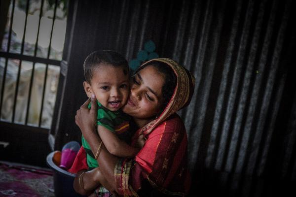 Mother Mina, 19, holding her son in their village in Muladi Upazila, Barasil district, Bangladesh.