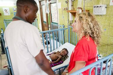 Dr Ellie Cannon talks with Dr Jean-Serge Botali at the bedside Femi*, 2, who was admitted to hospital with pneumonia and tuberculosis in the Democratic Republic of Congo (DRC). See herefor content.