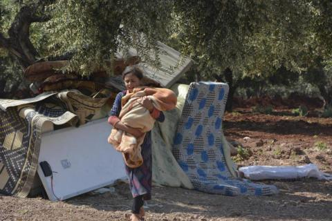 A young girl who has fled fighting in Idlib carries a baby in the temporary camp where she is staying