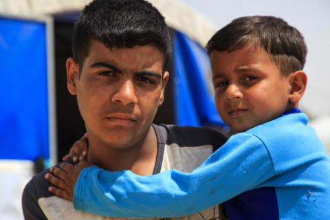 Jad 13 years old holding his little brother Maher 4 years old inside their tent in a camp for internal displaced people where they currently live after fleeing their home in W Mosul. Ahmad Baroudi/Save the Children