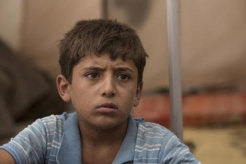Yacoub*, 12, from Raqqa, Syria, sits inside the tent in which he and his family now live, in a camp for people displaced by the war against ISIS in Syria.