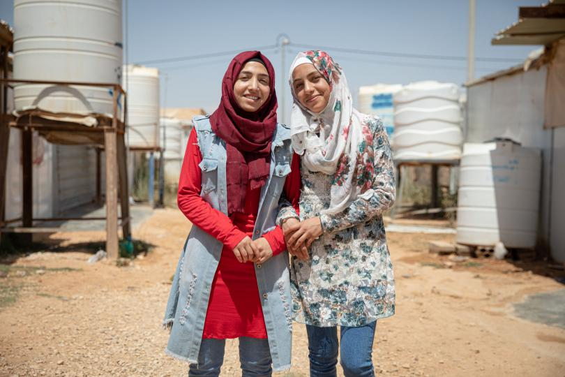 Hiba* (red shirt), 17, and Rama*, 14, pose for a portrait outside their family caravan in Za'atari camp for Syrian refugees, Jordan.
