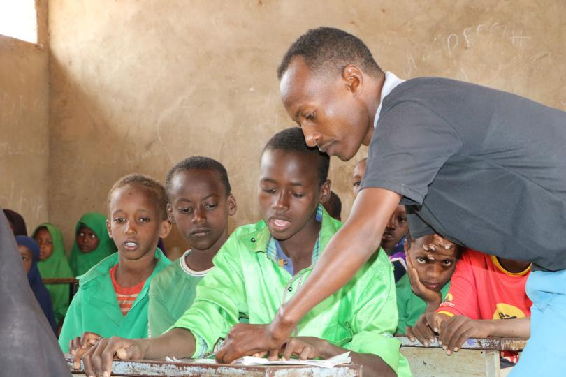 Teacher Mohammed helps children during science class in Somalia (before COVID-19)