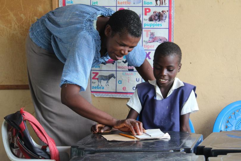 Kabukabu, 9, with her teacher at her local primary school, Zambia