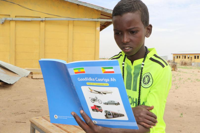 Nassir, 12, reads a book from Save the Children's mobile reading camp, when he is out of school because of the coronavirus, Ethiopia.