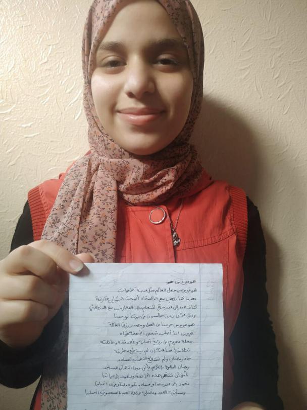 Mariam* holds her poem about coronavirus, Gaza