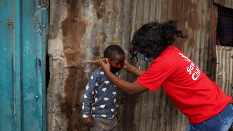 A Save the Children staff member helping a child wear his mask in Mathare slum, Kenya