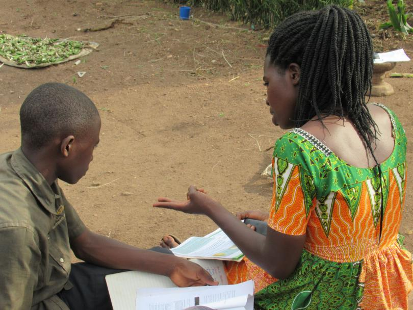 A teacher sits with a child in Uganda