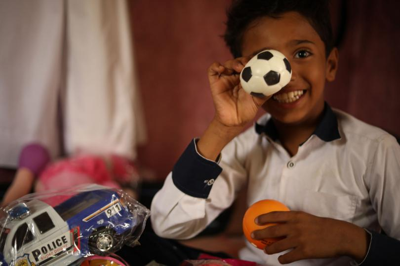 Aiman*, 12, plays with toys in his home in Yemen. Aiman* has brain atrophy which makes it difficult for him to move, walk or write. He loves school but is frustrated that he relies on the teachers to write the answers for him. Since COVID-19, Aiman's school has been closed.