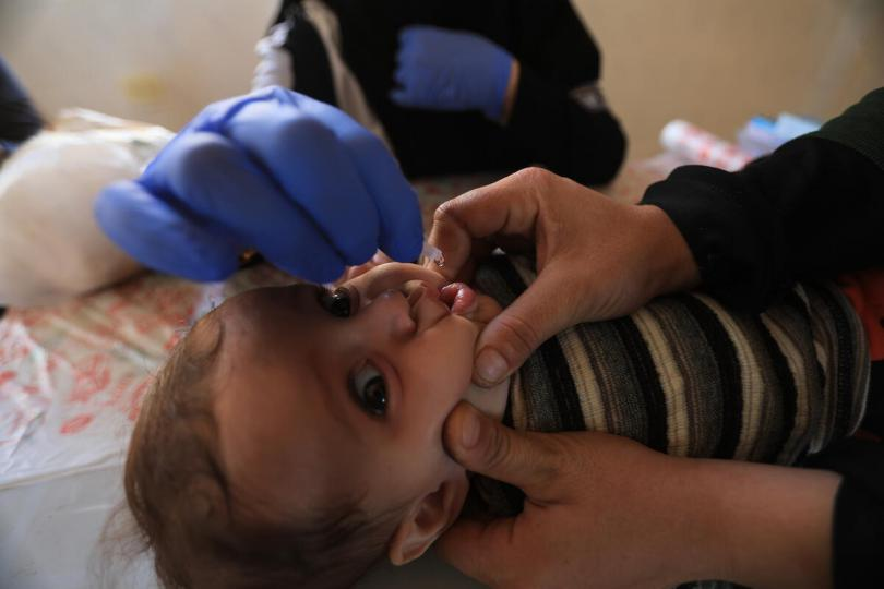 Mazen*, three months old, receiving an oral vaccine in a tent in North West Idlib, Syria