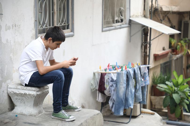 Jad*, 14, plays on his phone outside his home in Beirut, Lebanon