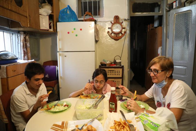 Mum Marie-Helene, Jad*, 14, and Lama*, 11, sit down to a dinner of Taouk chicken, French fries and salad