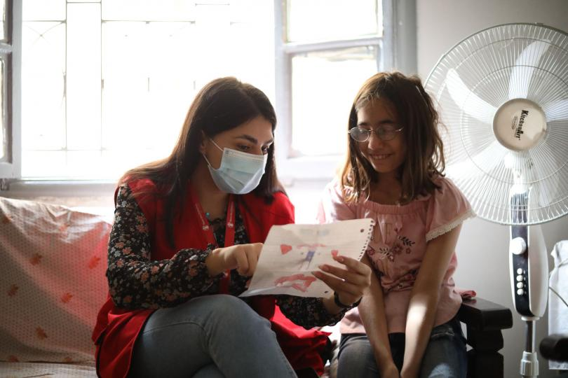 Case worker Hanaa discusses a drawing with Lama*, 11, Beirut, Lebanon