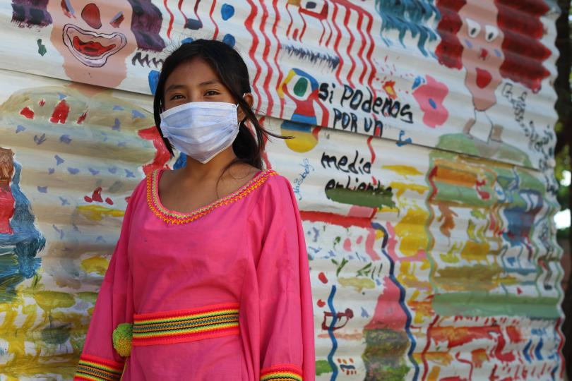 A young girl wears a face mask and looks to the camera, as she stand in front of a colourful wall of cartoon drawings