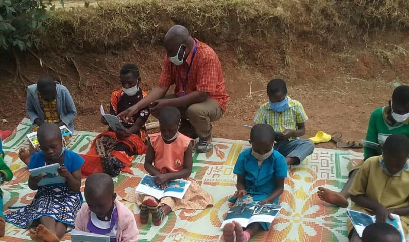 A community education worker supervising children during a free outdoor reading session, Rwanda