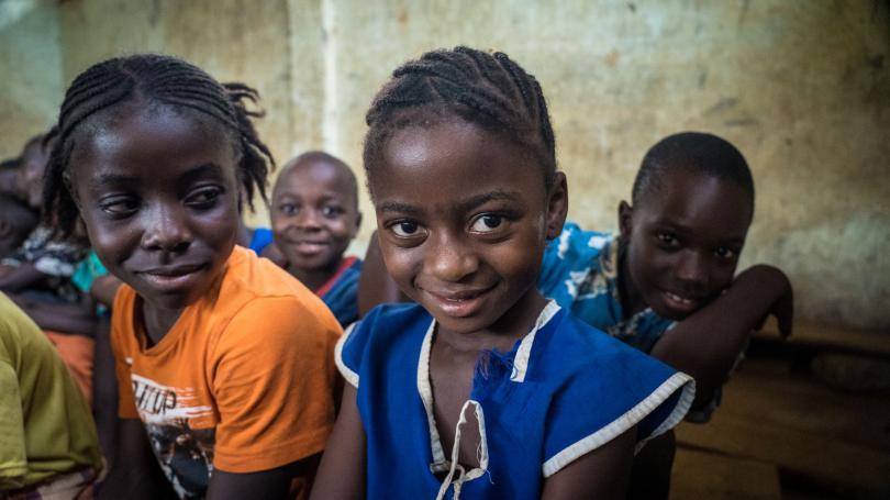 A girl smiles in her classroom in Sierra Leone