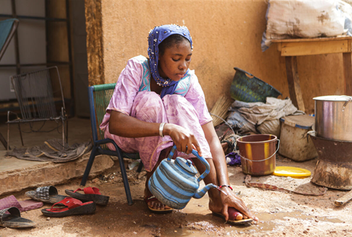 Kadidia*, aged 14, washes her feet outside her home in Mopti region, Mali.