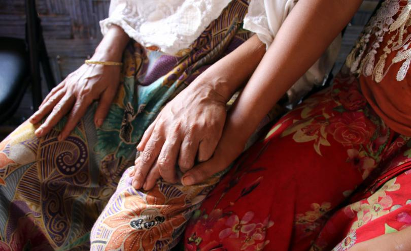 Child holds their mothers hand.