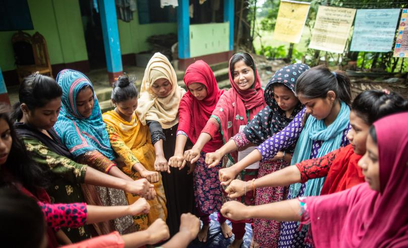 Young women's group standing in a circle putting their hands in the middle, Sylhet, Bangladesh