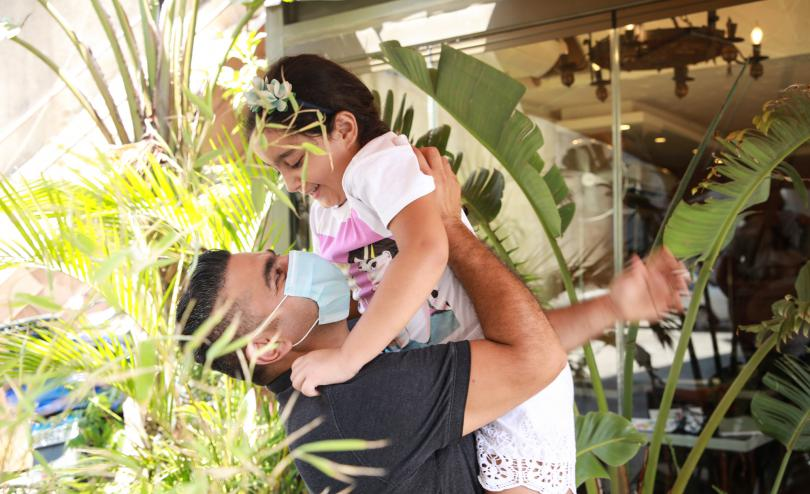 Sami* lifts up his daughter Layla*, 9, and hugs her in the garden of their home, surrounded by plants, in Beirut, Lebanon