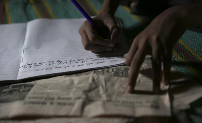 Tomal * writing at his shelter in Cox's Bazar