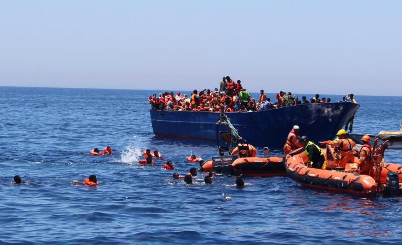Terrifying moment when desperate refugees and migrants fall in the water from an overcrowded wooden boat in the central Med 2017