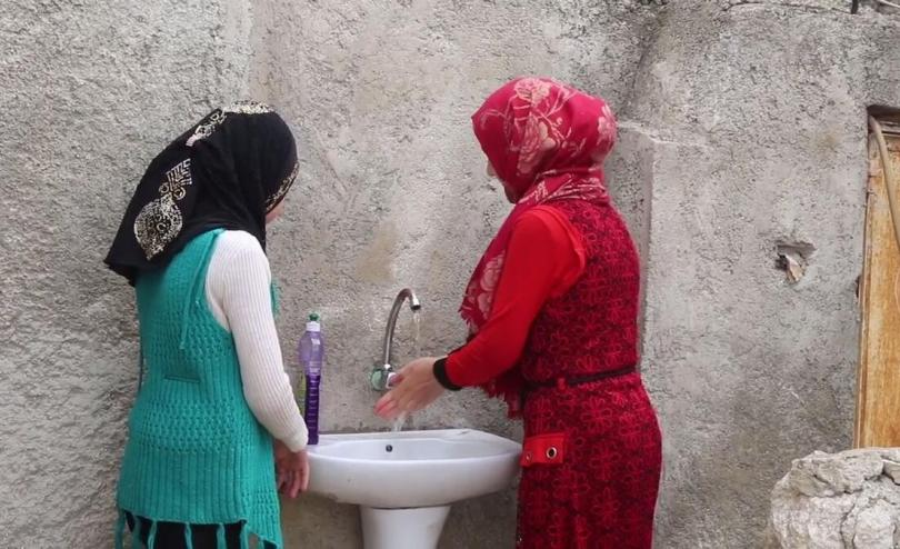 Cousins Zina*, 10, and Nawal*, 14, wash their hands, North West Syria