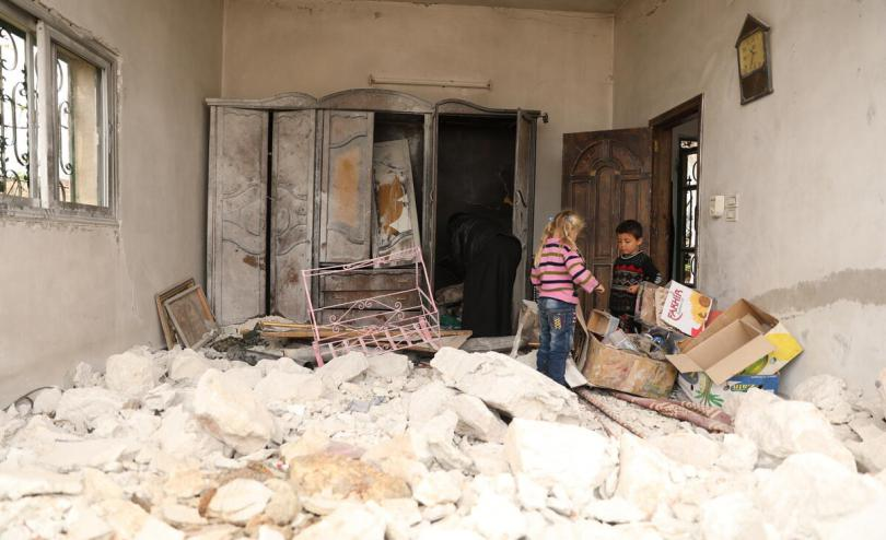 Ayman* with his grandchildren in their damaged home