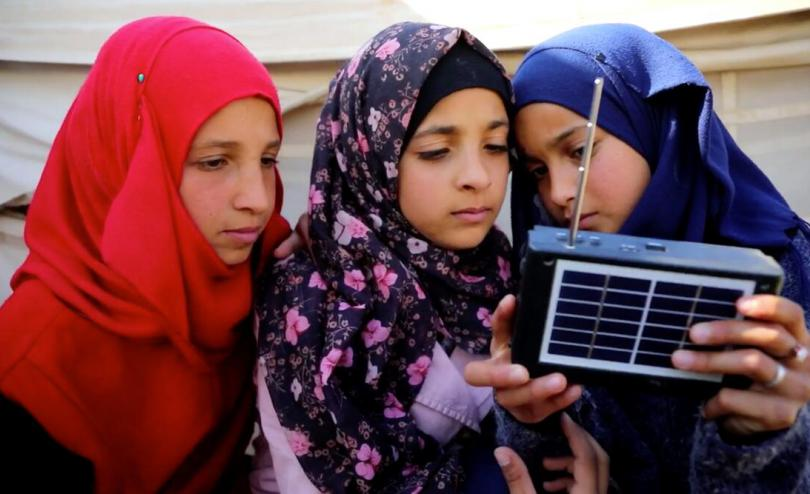 Nour*, 12 listening to the radio with her friends Lina* (left), 11 and Maha* (right), 12