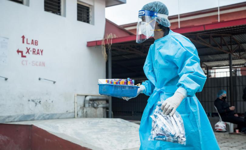 Health worker carries COVID-19 test samples, Nepal, May 2021