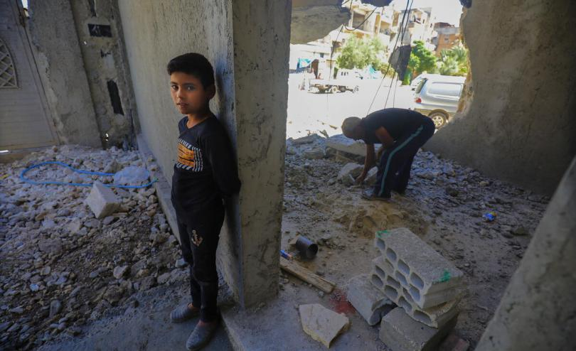 Yaseen* 12 with his father Fawaz* 43, in the house they are rebuilding