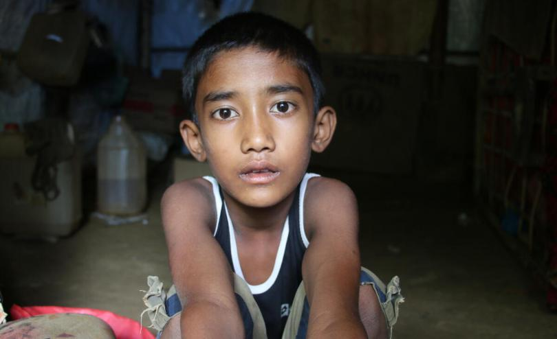 Aslam*, 8, a Rohingya refugee in his flood damaged home in Cox's Bazar