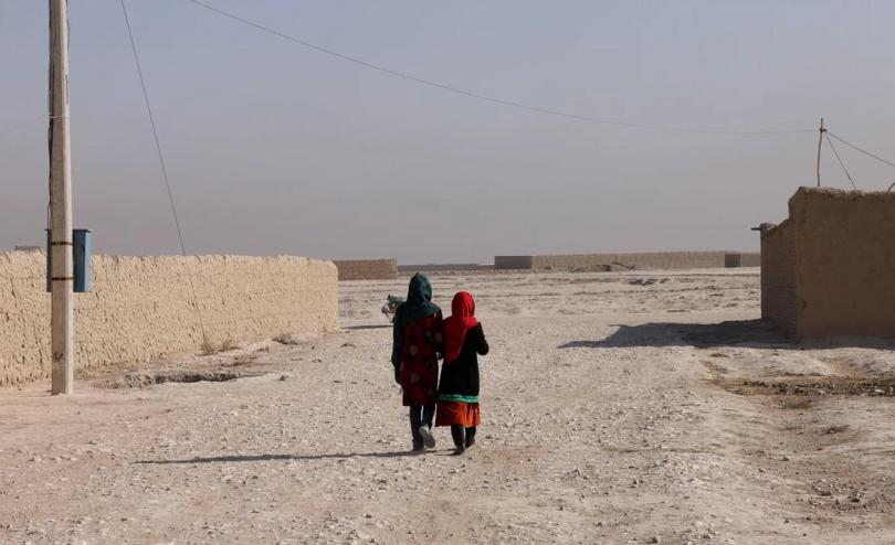 Two Afghan children walk down a street, photographed from behind
