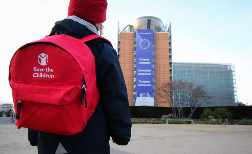 Child outside European commission with back to school kit