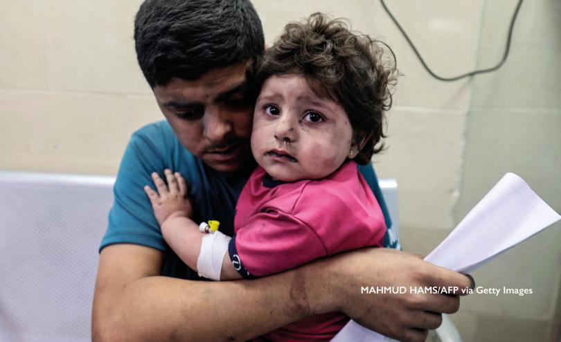 A child in Gaza is held by her father. MAHMUD HAMS/AFP via Getty Images