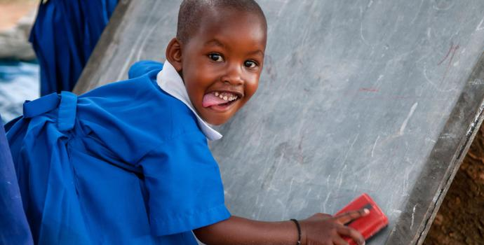 Girl smiles as she wiped a blackboard clean