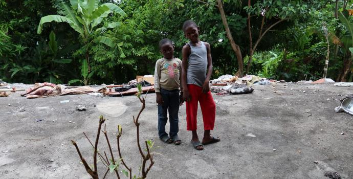 Samuel*, 8, and Evens, 6* at the site in Camp Perrin where their house used to stand