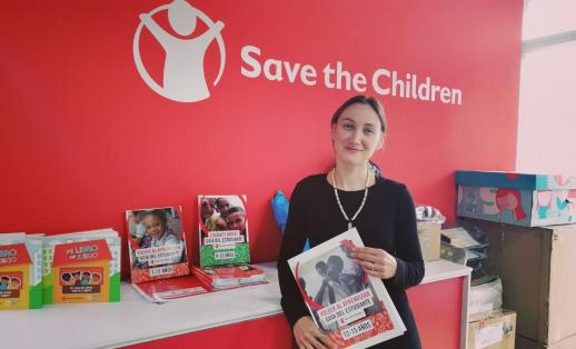 Ayse stands in front of the Save the Children logo, holding some of the books used in the temporary learning centre