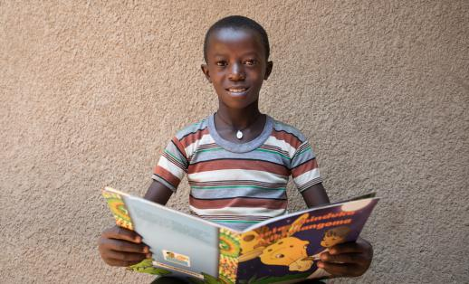 Wilson, 10, reading a book outside his reading club, Rwanda