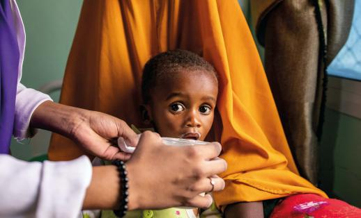 Nala* (20) holds her son Ahmed* (1) while Muna (23) gives him therapeutic milk at a Save the Children-supported stabilisation centre in Somalia