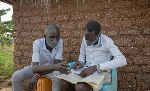 Two children reading with face masks on