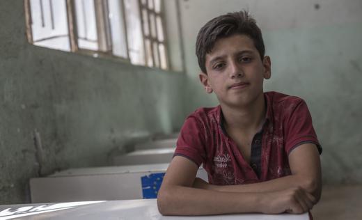 Fahad*, 12, in his damaged school in West Mosul, Iraq