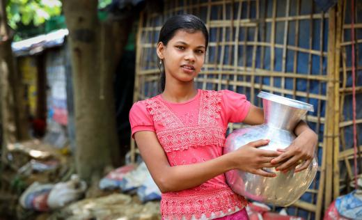 Ayesha,* age 12, holds a water container in Cox's Bazar, Bangladesh. The first confirmed case of coronavirus was reported in Cox Bazar, where one million Rohingya refugees have been sheltering in sprawling camps since August 2017.