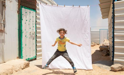 Faisal*, 5, poses for a portrait outside his family caravan in Za'atari camp for Syrian refugees, Jordan.