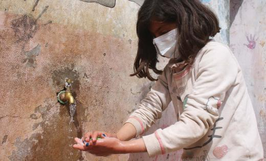 Tala*, 9 washing her hands in a camp in northern Idlib in Syria