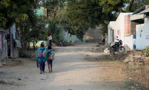 Sandhya, 13, and her brother Shivaji, 8, walk home from their school which has Save the Children supported beautified classrooms with teaching and learning materials