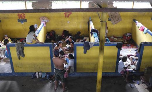 Families eating and resting at Bauan Cockpit Arena which now serves as an evacuation centre