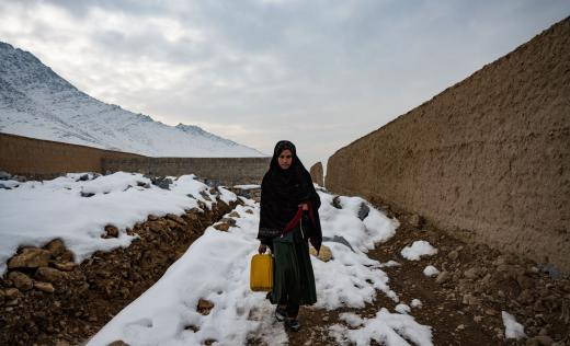 A girl fetches water for the household before going to a school sponsored by Save The Children in a village outside of Kabul
